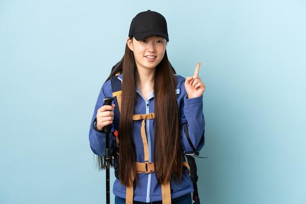 Jovem chinesa com pólos de mochila e trekking sobre parede azul isolada, mostrando e levantando um dedo em sinal dos melhores Foto Premium