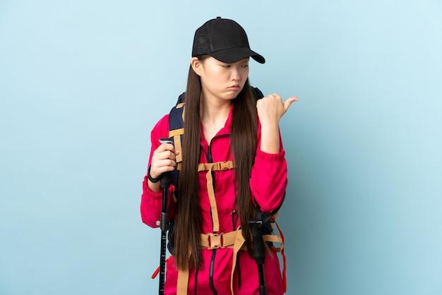 Jovem chinesa com polos mochila e trekking sobre parede azul infeliz e apontando para o lado