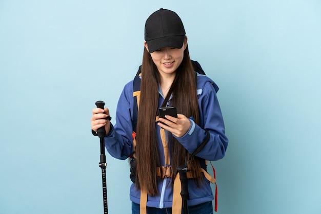 Jovem chinesa com polos mochila e trekking sobre parede azul isolada, enviando uma mensagem com o celular