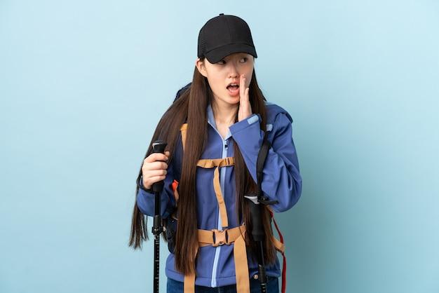 Jovem chinesa com polos mochila e trekking sobre parede azul isolada sussurrando algo com gesto de surpresa enquanto olha para o lado