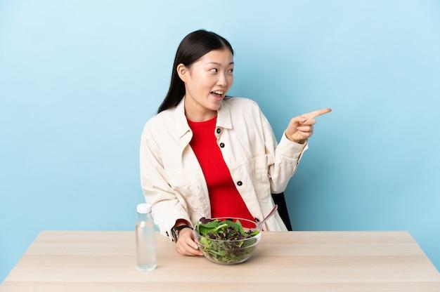 Jovem chinesa comendo uma salada, apontando o dedo para o lado e apresentando um produto