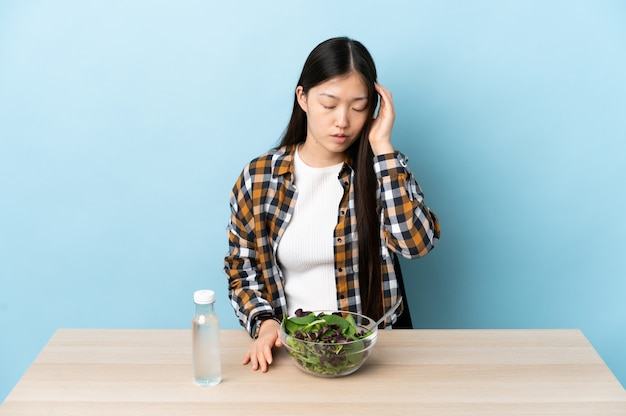 Jovem chinesa comendo uma salada com dor de cabeça