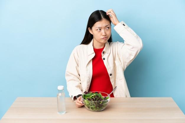 Jovem chinesa comendo uma salada com dúvidas enquanto coça a cabeça