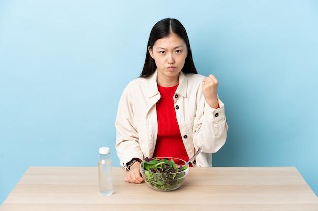 Jovem chinesa comendo uma salada com expressão infeliz