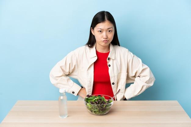 Jovem chinesa comendo uma salada com raiva