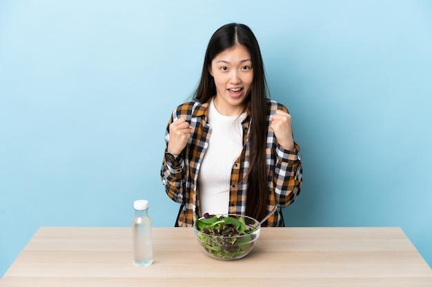 Jovem chinesa comendo uma salada comemorando a vitória na posição de vencedora