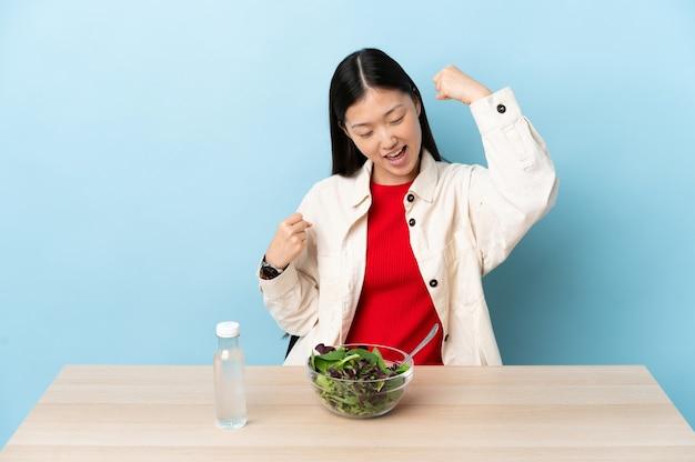 Jovem chinesa comendo uma salada comemorando uma vitória