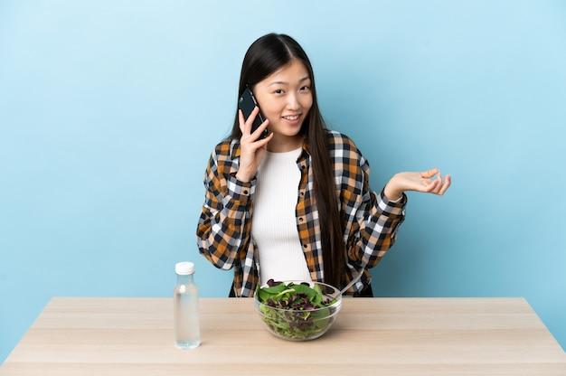 Jovem chinesa comendo uma salada, conversando com alguém ao telefone celular