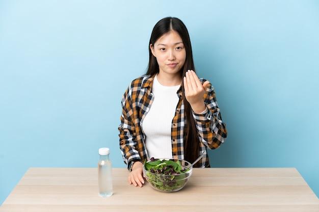 Jovem chinesa comendo uma salada convidativa para vir com a mão. feliz que você veio