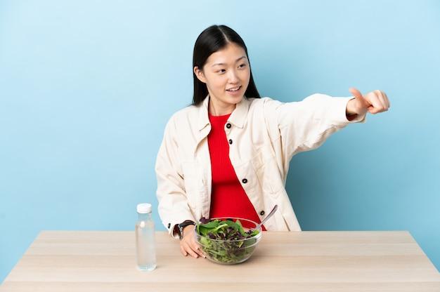Jovem chinesa comendo uma salada dando um polegar para cima gesto