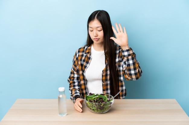 Jovem chinesa comendo uma salada fazendo um gesto de pare e desapontada
