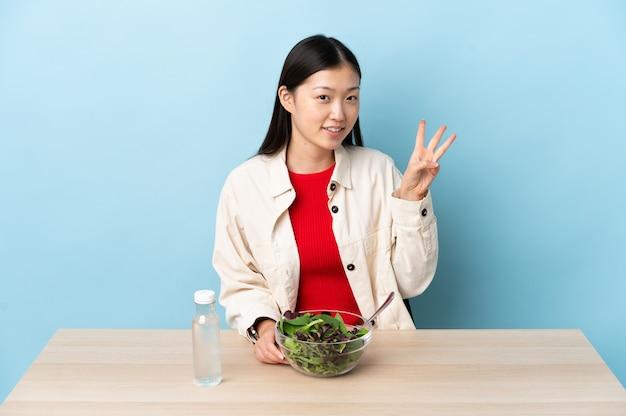 Jovem chinesa comendo uma salada feliz e contando três com os dedos