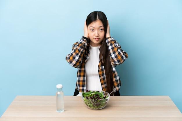 Jovem chinesa comendo uma salada frustrada e cobrindo as orelhas