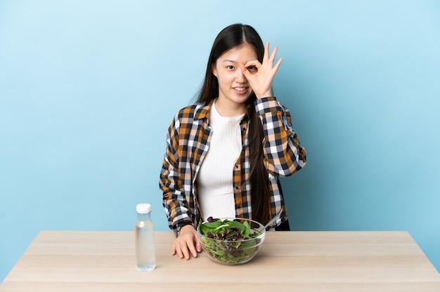 Jovem chinesa comendo uma salada, mostrando sinal de ok com os dedos