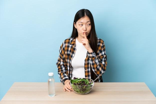 Jovem chinesa comendo uma salada, mostrando um sinal de silêncio, gesto de colocar o dedo na boca