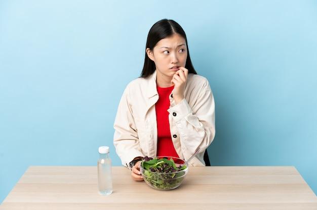 Jovem chinesa comendo uma salada nervosa e assustada
