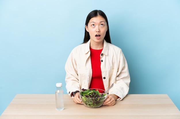 Jovem chinesa comendo uma salada olhando para cima e com expressão de surpresa