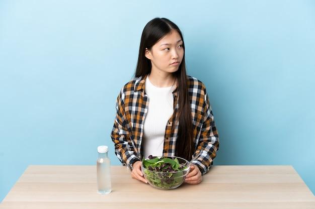 Jovem chinesa comendo uma salada olhando para o lado