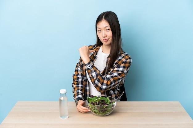 Jovem chinesa comendo uma salada orgulhosa e satisfeita