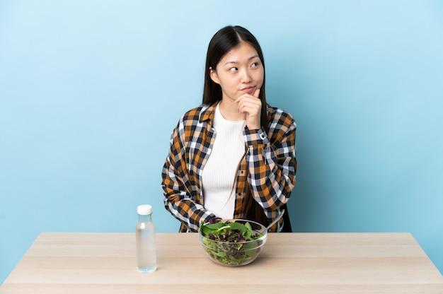 Jovem chinesa comendo uma salada pensando em uma ideia enquanto olha para cima