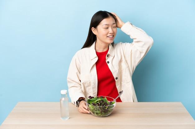 Jovem chinesa comendo uma salada sorrindo muito