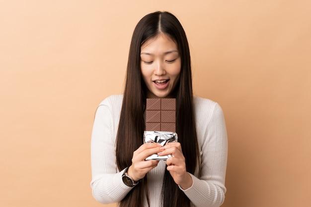 Jovem chinesa comendo uma tablete de chocolate