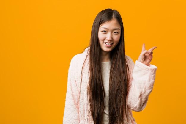 Jovem chinesa de pijama alegre e despreocupada, mostrando um símbolo de paz com os dedos