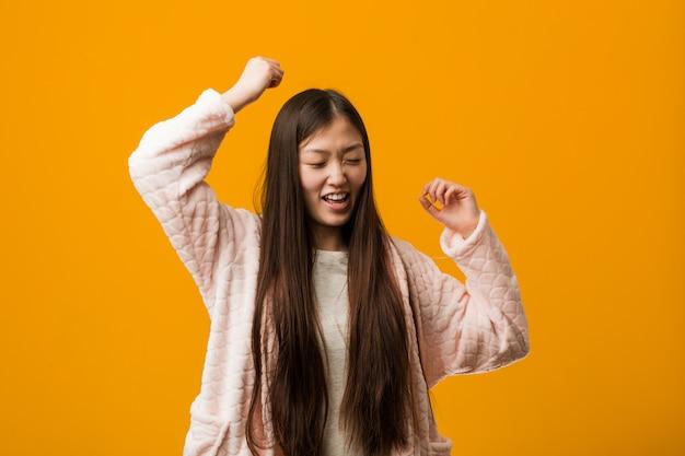 Jovem chinesa de pijama, comemorando um dia especial, saltos e levantando os braços com energia.