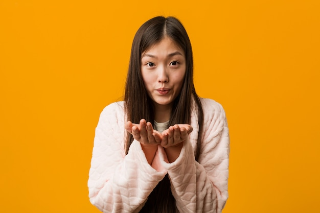 Jovem chinesa de pijama, dobrando os lábios e segurando as palmas das mãos para enviar beijo de ar.