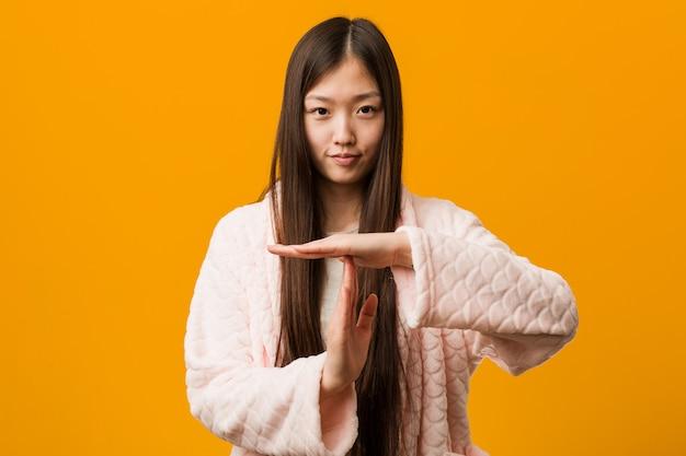 Jovem chinesa de pijama mostrando um gesto de tempo limite