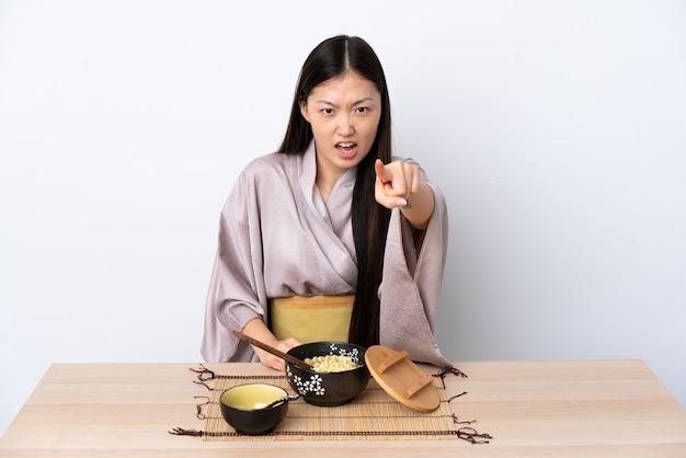 Jovem chinesa de quimono a comer macarrão frustrada e a apontar para a frente