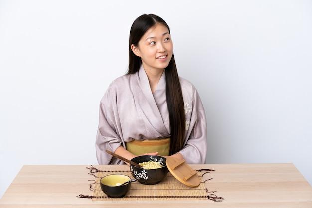 Jovem chinesa de quimono comendo macarrão, tendo uma ideia enquanto olha para cima