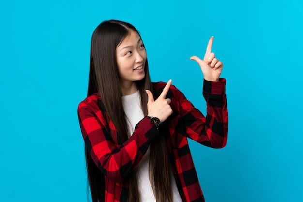 Jovem chinesa em azul isolado apontando com o dedo indicador uma ótima idéia
