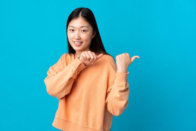 Jovem chinesa em azul isolado apontando para o lado para apresentar um produto