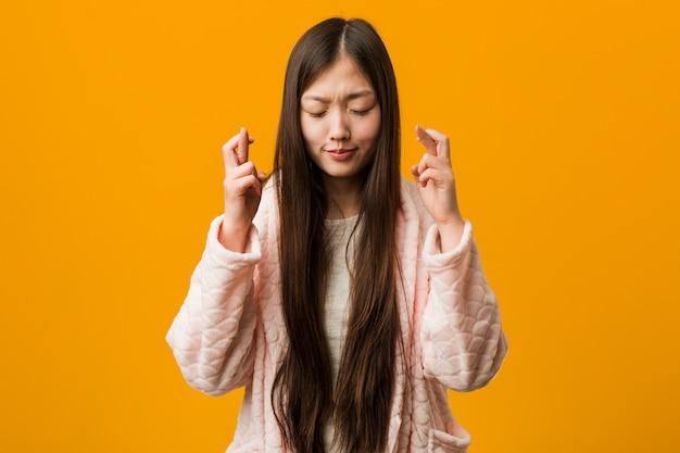 Jovem chinesa em dedos de cruzamento de pijama por ter sorte