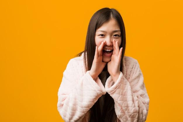Jovem chinesa em pijama gritando animado para a frente.
