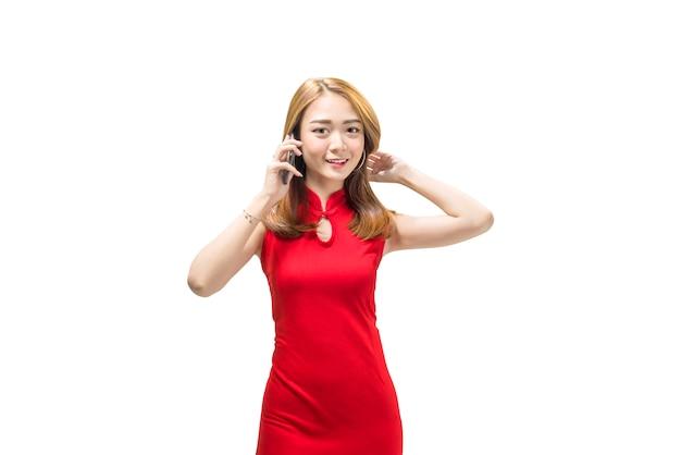 Jovem chinesa em roupas tradicionais em pé e falando no celular