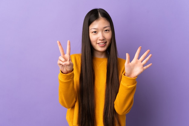 Jovem chinesa em roxo isolado contando sete com os dedos
