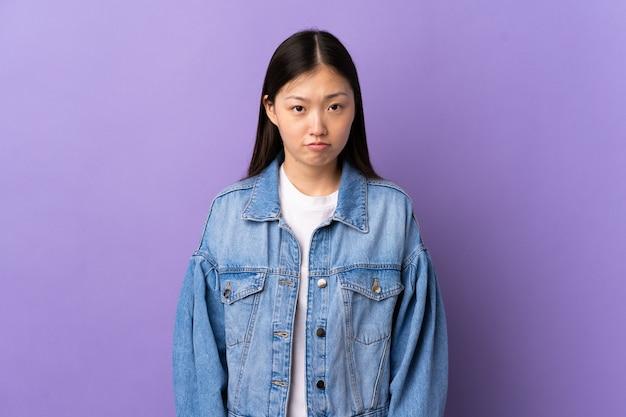 Jovem chinesa em um roxo isolado com uma expressão triste