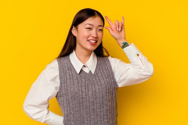 Jovem chinesa isolada em amarelo, mostrando um gesto de chifres como um conceito de revolução.