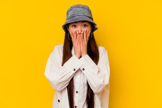 Jovem chinesa isolada em um fundo amarelo chocada, cobrindo a boca com as mãos, ansiosa para descobrir algo novo.