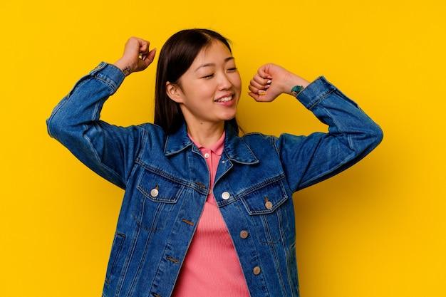 Jovem chinesa isolada em um fundo amarelo comemorando um dia especial, pula e levanta os braços com energia.