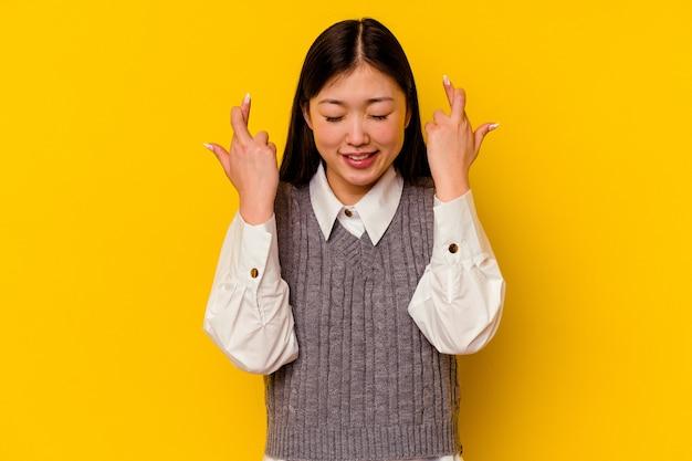 Jovem chinesa isolada em um fundo amarelo cruzando os dedos para ter sorte