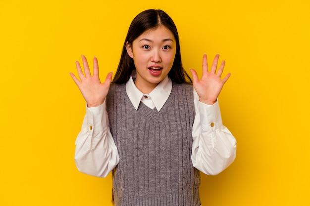 Jovem chinesa isolada em um fundo amarelo, gritando para o céu, olhando para cima, frustrada.