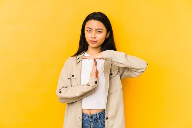 Jovem chinesa isolada em um fundo amarelo, mostrando um gesto de tempo limite.