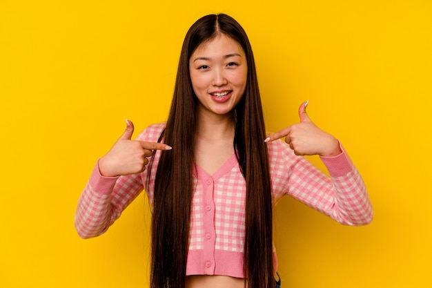 Jovem chinesa isolada em um fundo amarelo surpresa apontando com o dedo, sorrindo amplamente.