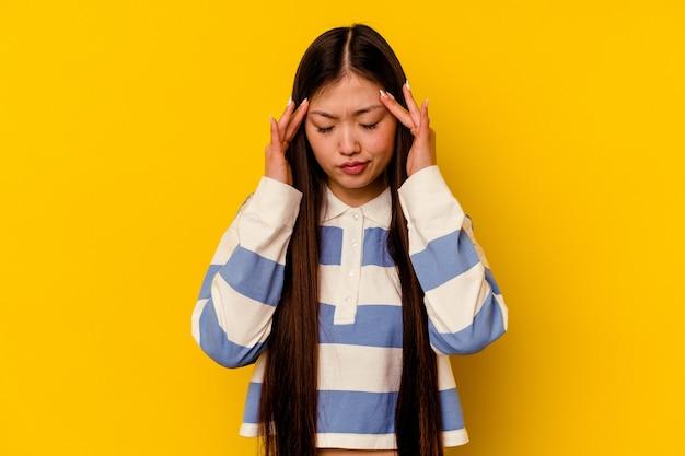 Jovem chinesa isolada em um fundo amarelo, tocando as têmporas e tendo dor de cabeça.