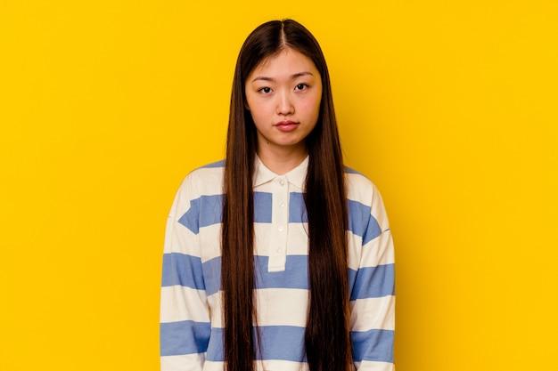 Jovem chinesa isolada em um fundo amarelo triste, rosto sério, sentindo-se miserável e descontente.