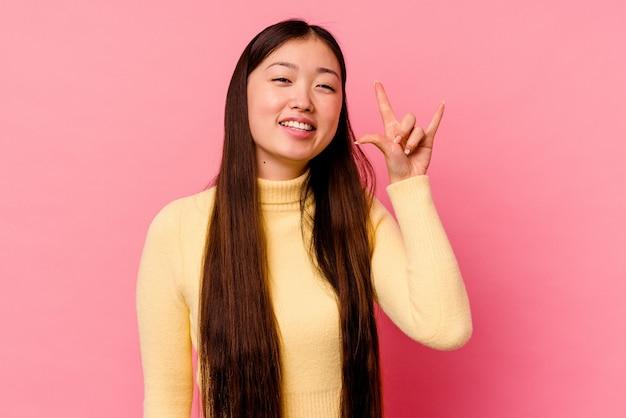 Jovem chinesa isolada em um fundo rosa, mostrando um gesto de chifres como um conceito de revolução.