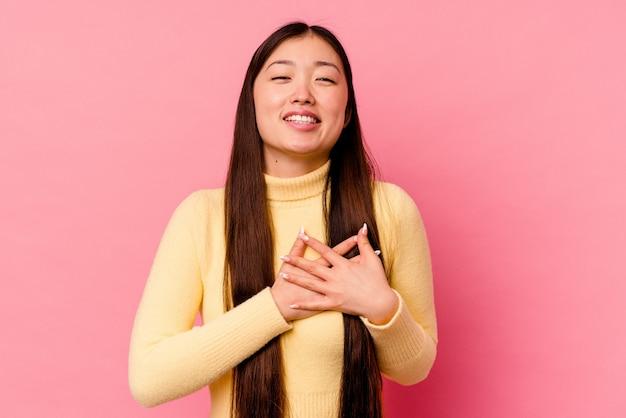 Jovem chinesa isolada em um fundo rosa tem uma expressão amigável, pressionando a palma da mão no peito. conceito de amor.